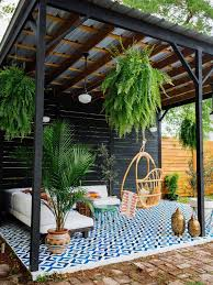 this 300 square foot covered backyard patio in new orleans louisiana features a sofa from west elm and the justina blakeney cohanga hanging chair