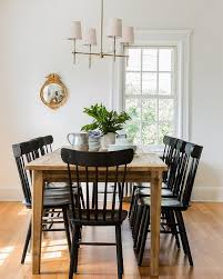 chic cote dining room features a farmhouse dining table lined with black salt chairs illuminated by a thomas o brien bryant chandel