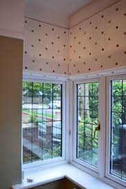 Clarke & Clarke embroidered spot fabric on 3 Roman Blinds in a square bay  window