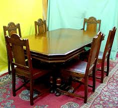 this handsome dark oak dining room set consists of a table that has a hidden fold away leaf and a set of 6 chairs one of which is a captain s chair