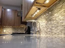 creative under cabinet lighting with modern backsplash tile