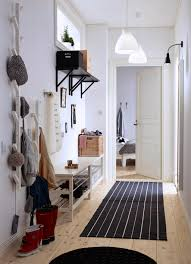 shoes furniture. a small hallway with two benches for shoes mirror and treeshaped hangers furniture