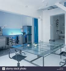 Glass Table And Black Swivel Chairs In Dining Area In Open Plan