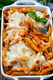 en parmesan pasta in a baking dish topped with melted cheese and garnished with fresh basil