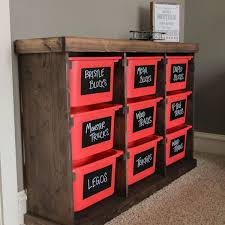 a wooden toy storage chest with red bins