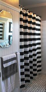 appealing striped shower curtain with beadboard walls and wall mirror plus towel rack