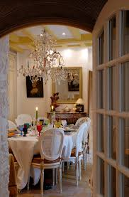 paris villa 1032 dining area has a real candle chandelier hanging under a traditional beamed ceiling