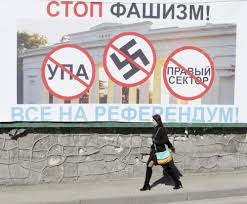 explanations for the russian kyiv junta myth euromaidan press a w walks past a billboard advertising the crimean referendum and calling to stop fascism