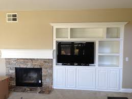 interior grey stone fireplace with white mantel shelf connected by white wooden tv cabinet and