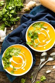two bowls of roasted ernut squash soup with a drizzle of coconut milk with two spoons