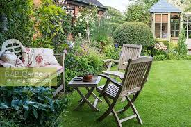 a cottage garden with shady seating area summer house lawn and mixed borders with