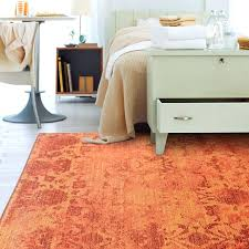 pink and orange rug add vibrancy and color to a neutral bedroom with a bright orange pink and orange rug