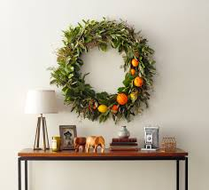 a beautiful wreath of greenixed fresh citrus over a foyer table