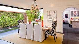 terranean dining room with white slipcovered dining chairs unique chandelier and large rug