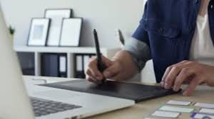 graphic designer home office. subscription library closeup of freelance graphic designer sketching on tablet working from home ofice office