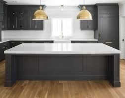 black kitchen cabinets with white quartz countertop white oak hardwood floor brass accents and