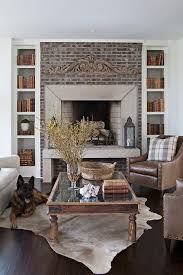 cottage living room features a brick fireplace with hearth flanked by narrow alcoves filled with bookshelves