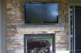 interior grey stone mantel shelf under rectangle black led tv on brown stone fireplace