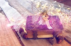 image of magical little fairy in the forest next to old story book vine filtered with glitter overlay photo by tomert