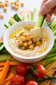 creamy homemade hummus in a small white bowl topped with olive oil peas and