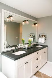 white bathroom cabinets with dark countertops. frame mirror and white cabinets the master bathroom has black granite countertops with double vanity sinks, a special bathtub given to homeowner, dark o