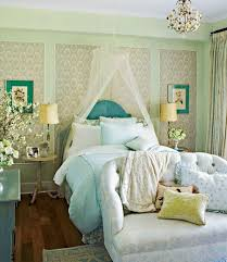 a tiny chandelier is a sweet addition above the tufted loveseat in this beautiful bedroom is that daisies i see among the crystals