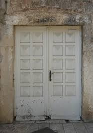 white wood door. Old Wooden Doors In White Color With Grid-patterned Surface And Dark Spots On Bottom Wood Door