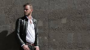 a man in his 20s wearing a black leather jacket and white shirt leaning back against a wall of stone on a sunny summer day