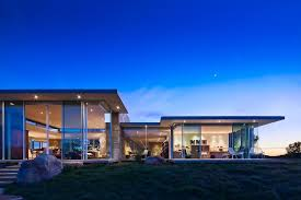 7 stars auto glass modern exterior also boulders flat roof floor to ceiling windows glass house glass wall grass lawn night lighting oversized windows patio