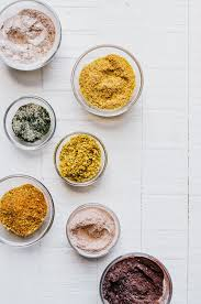 homemade popcorn seasoning in 7 flavors on a white wood background