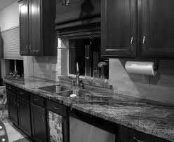 traditional black and white kitchen design ideas with dark wooden cabinetry also granite top
