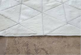 patchwork rug detail of white cowhide patchwork rug in triangles design on stone floor patchwork cowhide rugs australia