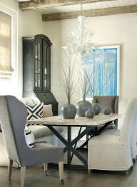 transitional dining room with x based table natural linen slipper chairs and gray captain captains chair