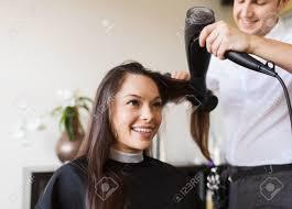 美しさ髪型と人々 のコンセプト 幸せな若い女とホット髪サロンでのスタイルのファンで美容院
