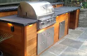 the finished design includes stainless steel outdoor kitchen appliances built into a bbq island lined with beautiful red cedar napa