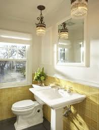 White and yellow bathroom with yellow bathroom tiles! Cream walls and  traditional white pedestal sink and toilet.