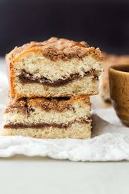 two slices of cinnamon crumb coffee cake stacked on white fabric