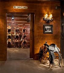 stunning wooden tack room filled with western saddles