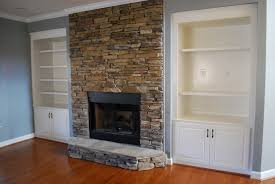 here is a stacked stone fireplace between two built in bookcases