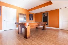 orange rug with eclectic basement and pool table light hardwood flooring industrial coffee table black chair orange