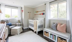 nursery freestanding window seat bench fitted with three open lower shelves designed with a set of books and wicker baskets for storage