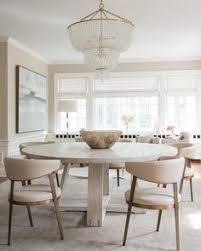 contemporary open plan dining room features an aerin jacqueline two tier chandelier hung above a round gray oak dining table surrounded by modern cream