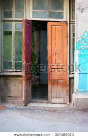 old wooden door open of a shabby demaged house facade or front in brown green
