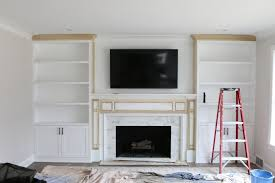 the process of installing whte built ins around a fireplace