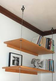 As an alternative to all that structural bulk, the maker decided to attach  the back of the shelves to the wall and suspend their fronts from the  ceiling via ...