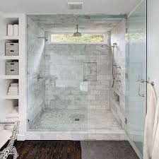 Master bath features walk-in shower accented with white marble subway tile  surround framing window