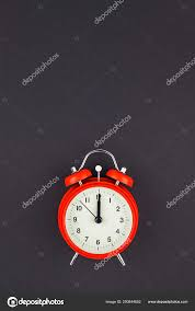 concept image of a red vintage alarm clock with twelve o clock on dark black color paper background with copy space in minimal style template for text