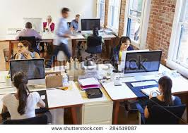 office photos. wide angle view of busy design office with workers at desks photos