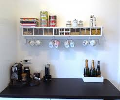 wall mounted kitchen shelf made of wood with hook made of silver metal for cups