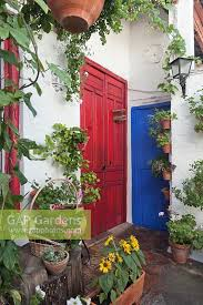 white painted patio corner with red and blue doors and terracotta pots of summer bedding plants